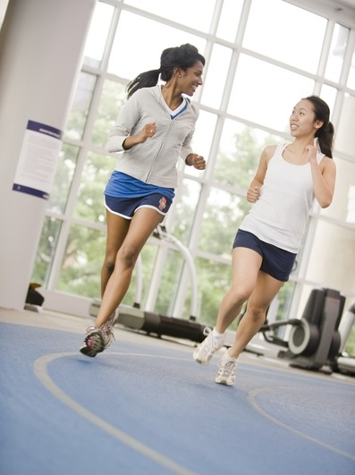 Two female students enjoy a jog on the Activities and Recreation Center track.