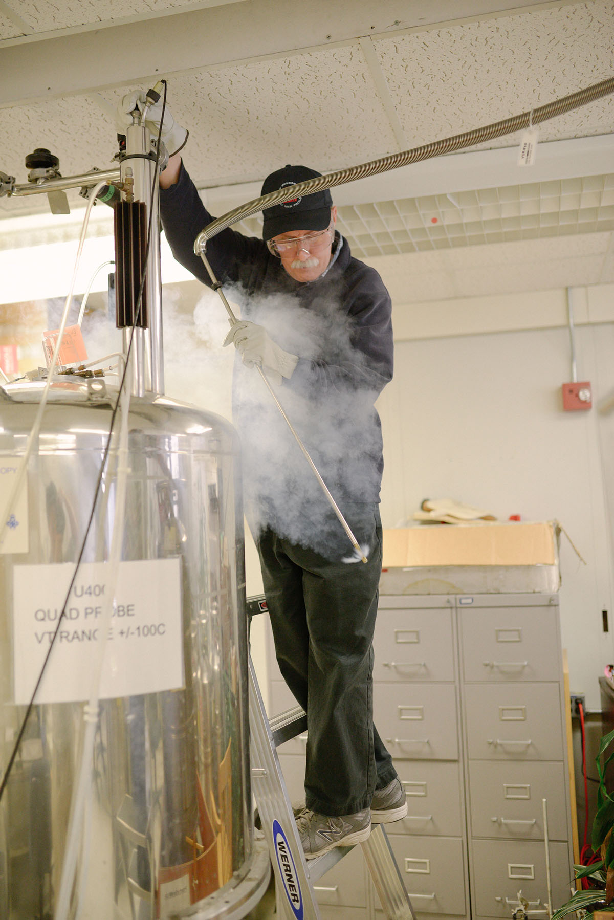 "NMR Lab Director Jerry Olson, surrounded by a ""plume"" of escaping helium gas, prepares to insert a liquid helium filler into a superconducting magnet apparatus. With the new recycling infrastructure in place, plumes and regular boil-off of helium will be captured, re-liquified and resupplied to magnets."