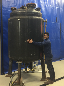 A member of the Illinois Biodiesel Initiative team stands next to a 50-gallon reactor, hugging it to show its size.
