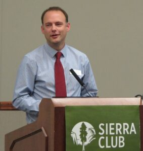 """A photo of Scott Tess delivering a presentation from behind a podium. Text on a banner hanging from the podium reads """"Sierra Club."""""""