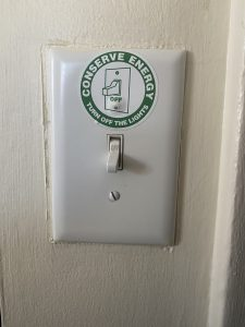 """The photo depicts a light switch with a sticker that reads """"Conserve Energy. Turn off the lights."""""""