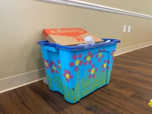 The photo depicts a recycling bin painted with flowers and grass.