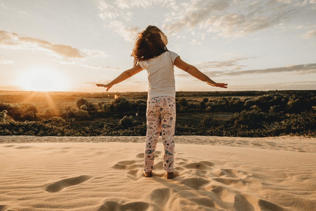 Framed by the light from a setting sun, a child stands with her back to us on top of a sand dune, arms outstretched as though she is flying. Footprints leading up to where she stands are visible in the sand.