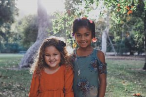 Two children stand smiling, side by side, in the middle of a greenspace. They are framed with sunlight.
